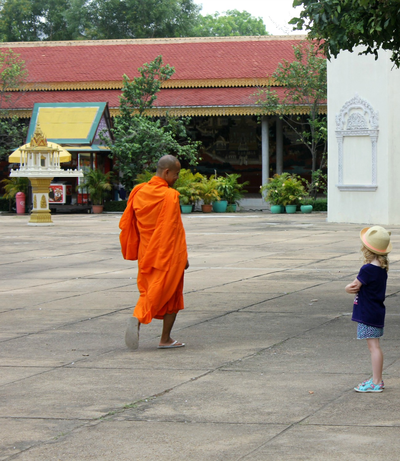 Monk and a girl looking at each other in the grounds of the Royal Palace at Phnom Penh - 12 reasons to visit Cambodia with kids