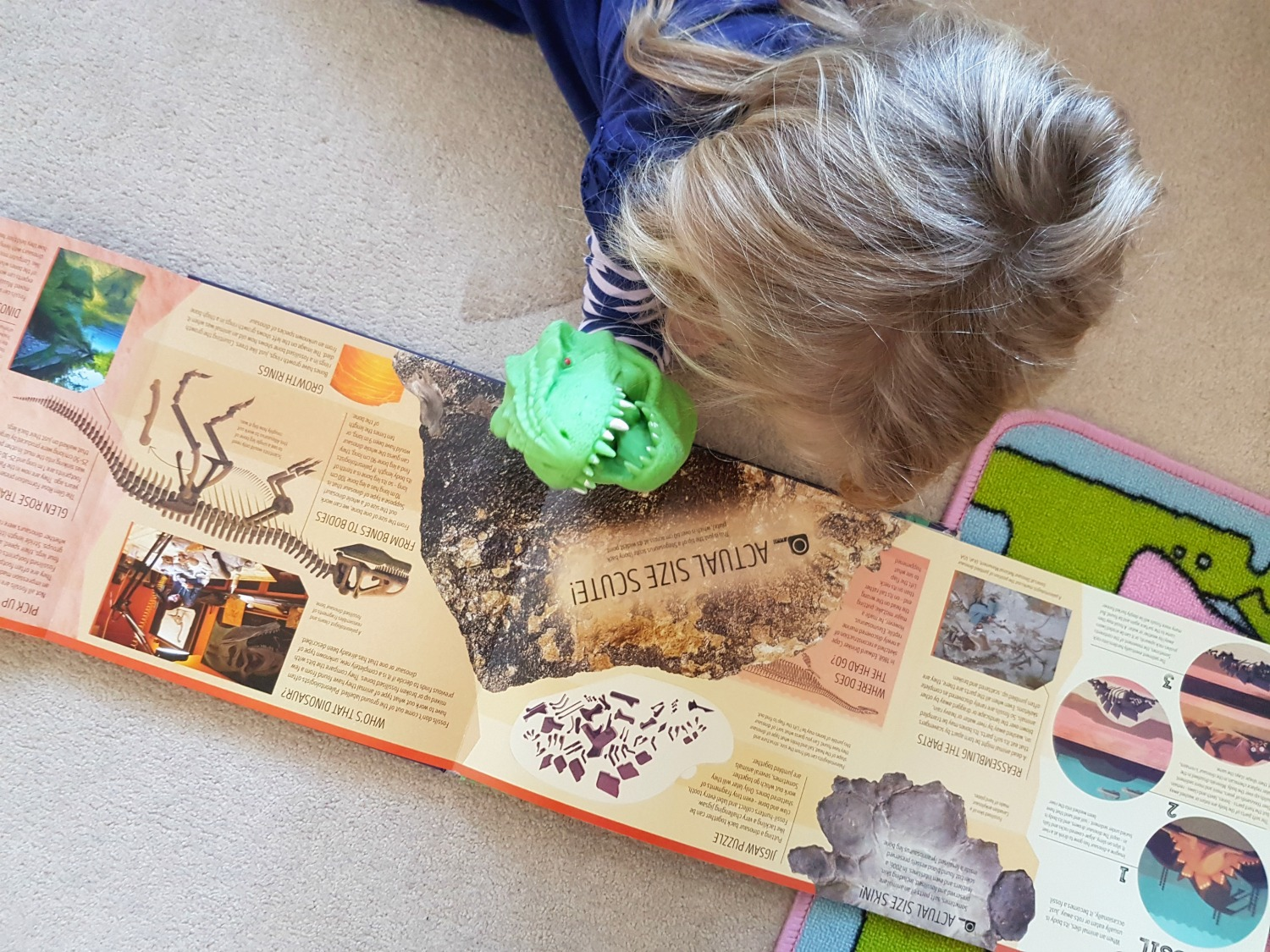 My daughter with her toy dinosaur reading the Lonely Planet Kids book Dinosaur Atlas - one of my November travel essentials