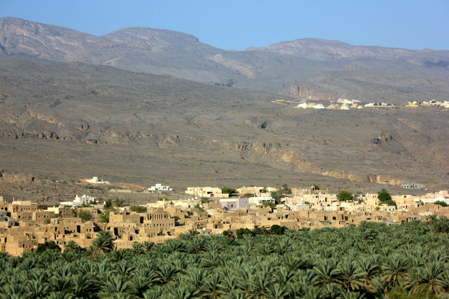 A view of the lush green date palms and a village in the wadi in the shadow of the Hajar Mountains in Oman - my nine reasons to visit Oman with kids