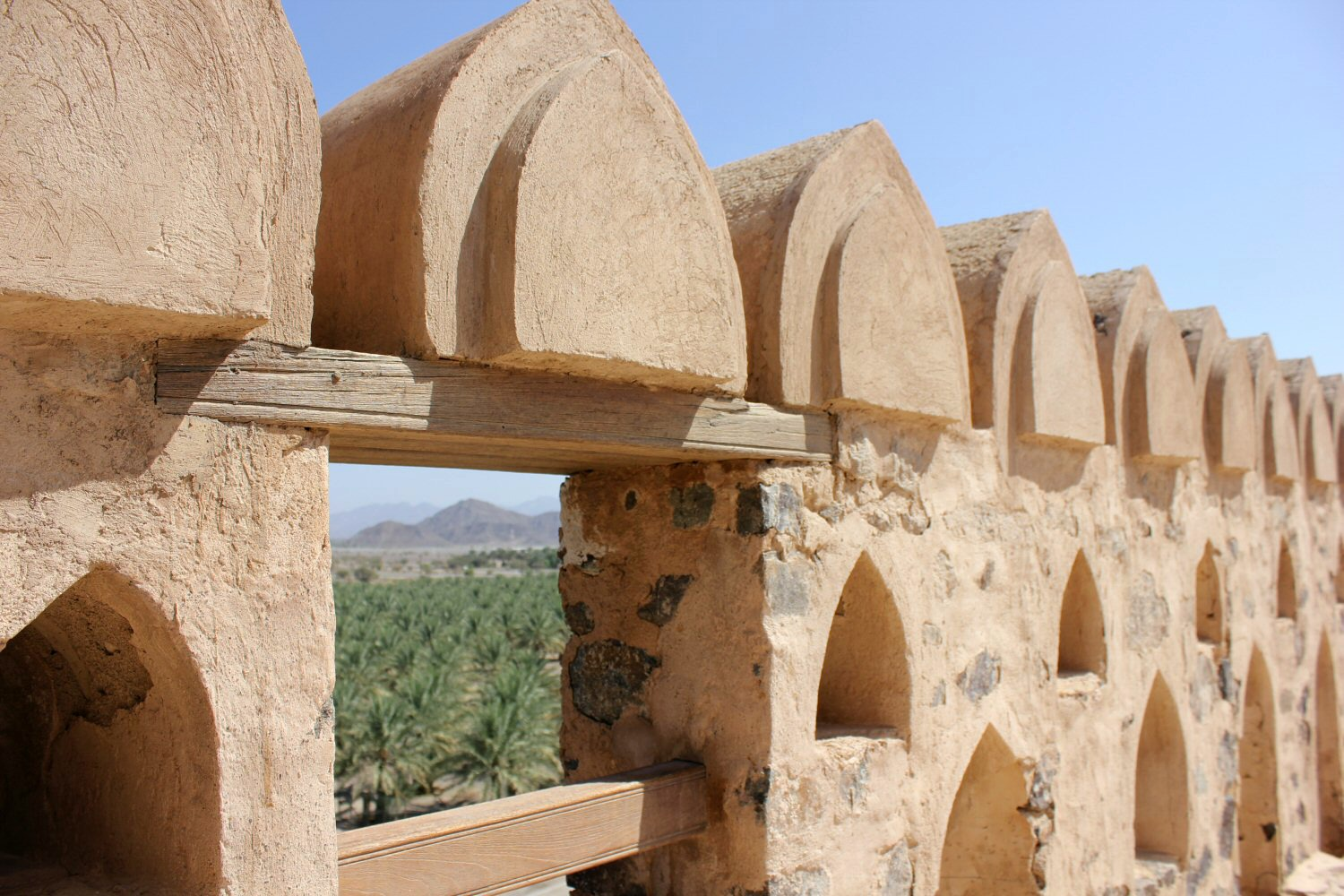 A view through the roof fortifications to palm trees from Jabrin Castle in Oman - my nine reasons to visit Oman with kids