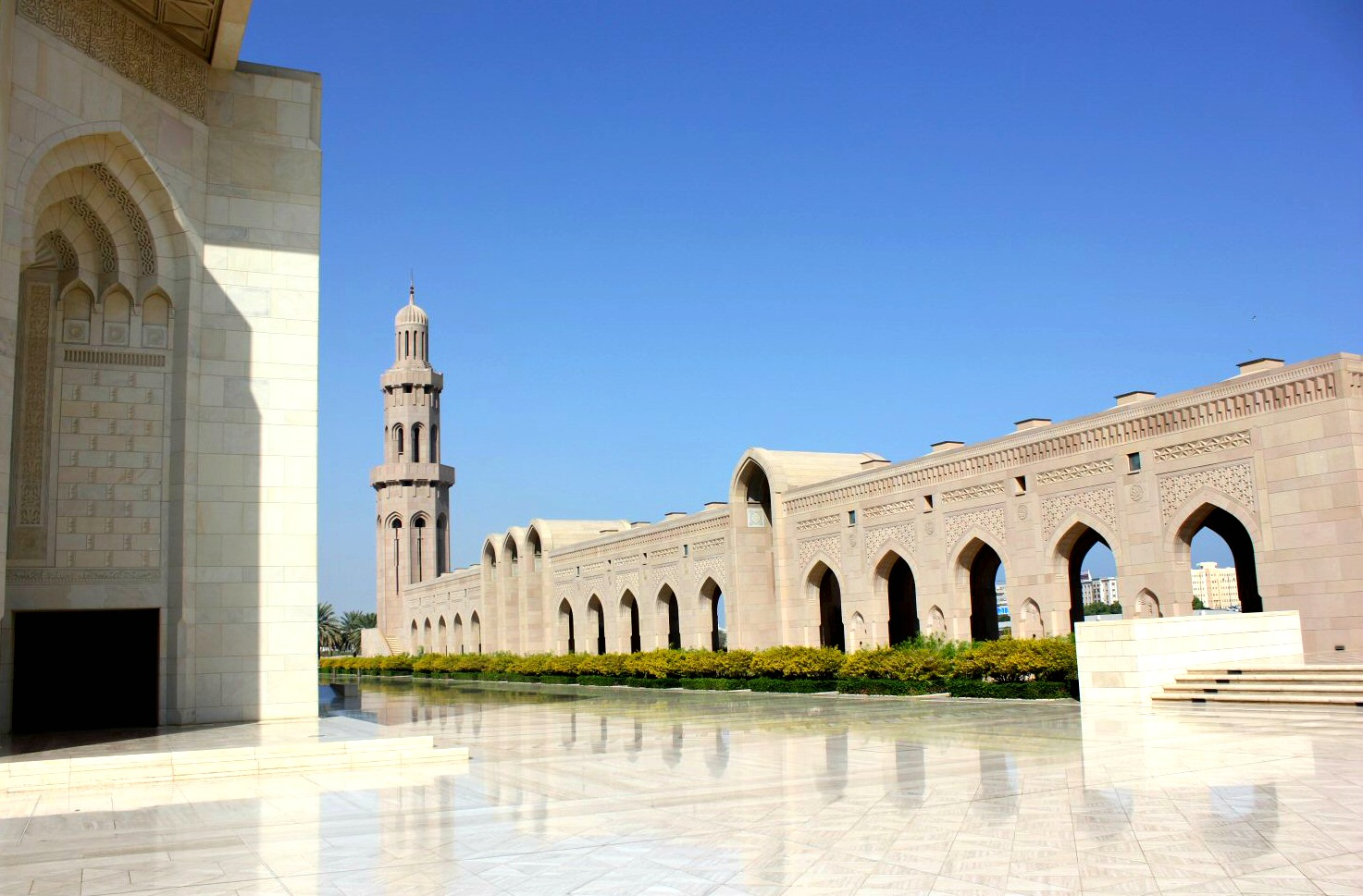 A view of a gleaming courtyard, minaret and buildings of the Sultan Qaboos Grand Mosque in Muscat Oman - the beautiful architecture is one of my nine reasons to visit Oman with kids