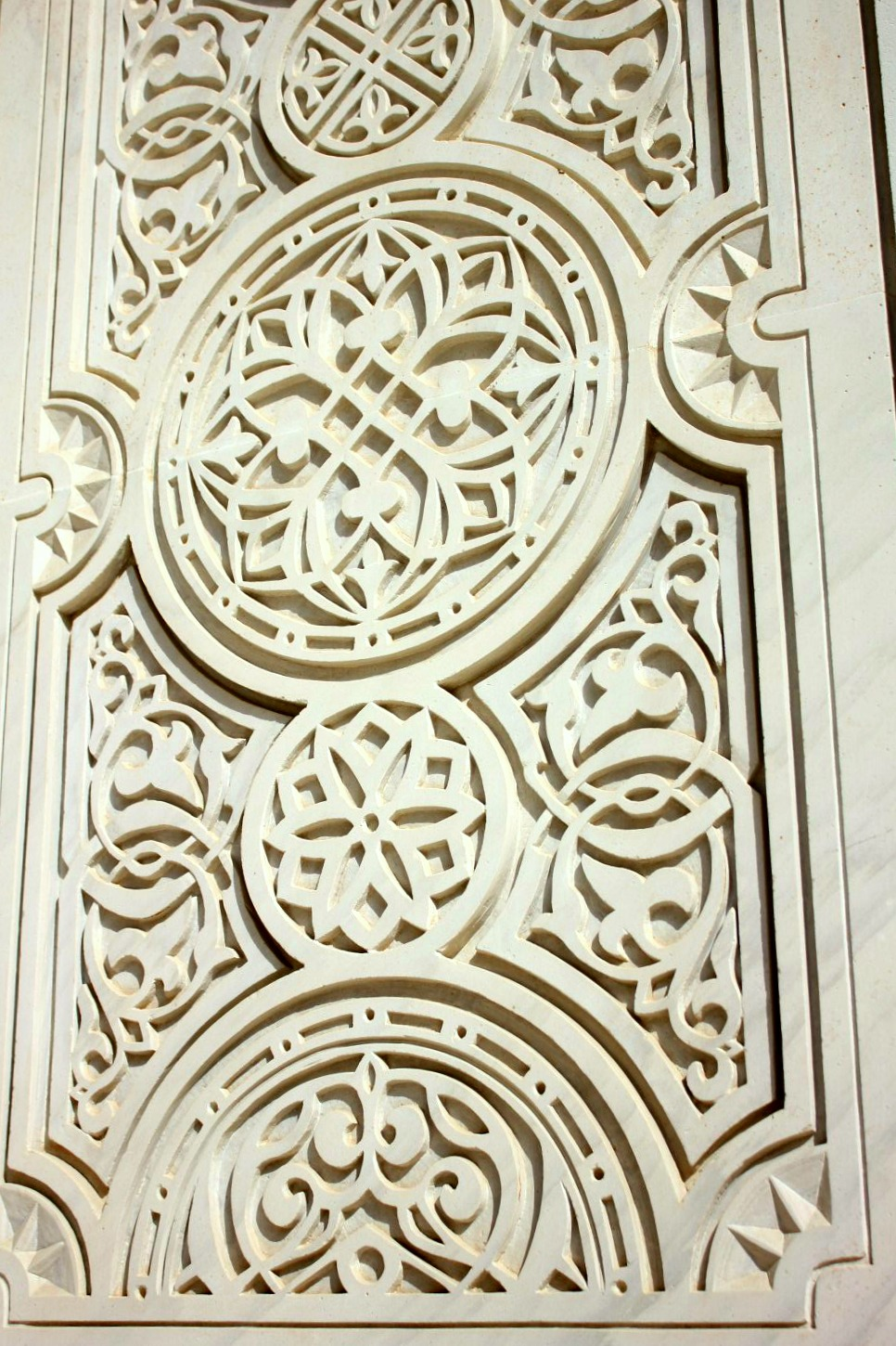 A view of some of the intricate geometric detailing on the white stone walls of the Sultan Qaboos Grand Mosque in Muscat Oman - the beautiful architecture is one of my nine reasons to visit Oman with kids