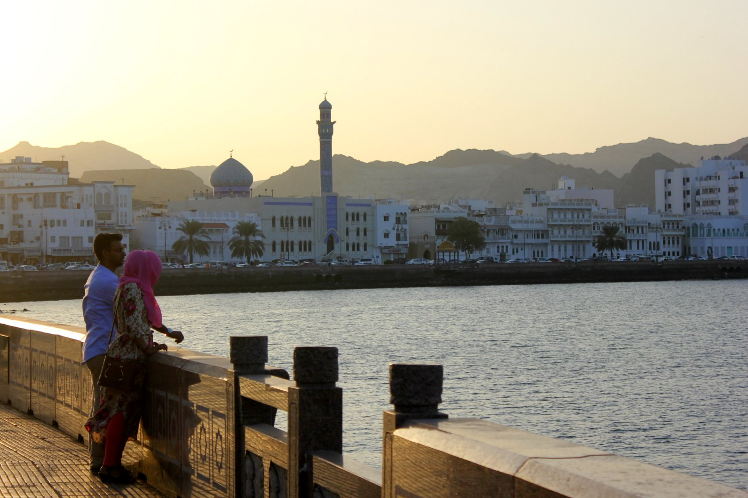 A view from the Corniche at Mutrah towards the sea and Muscat, a couple silhoutted against the sunset - how to explore the sprawling capital was one of my Oman travel lessons learned