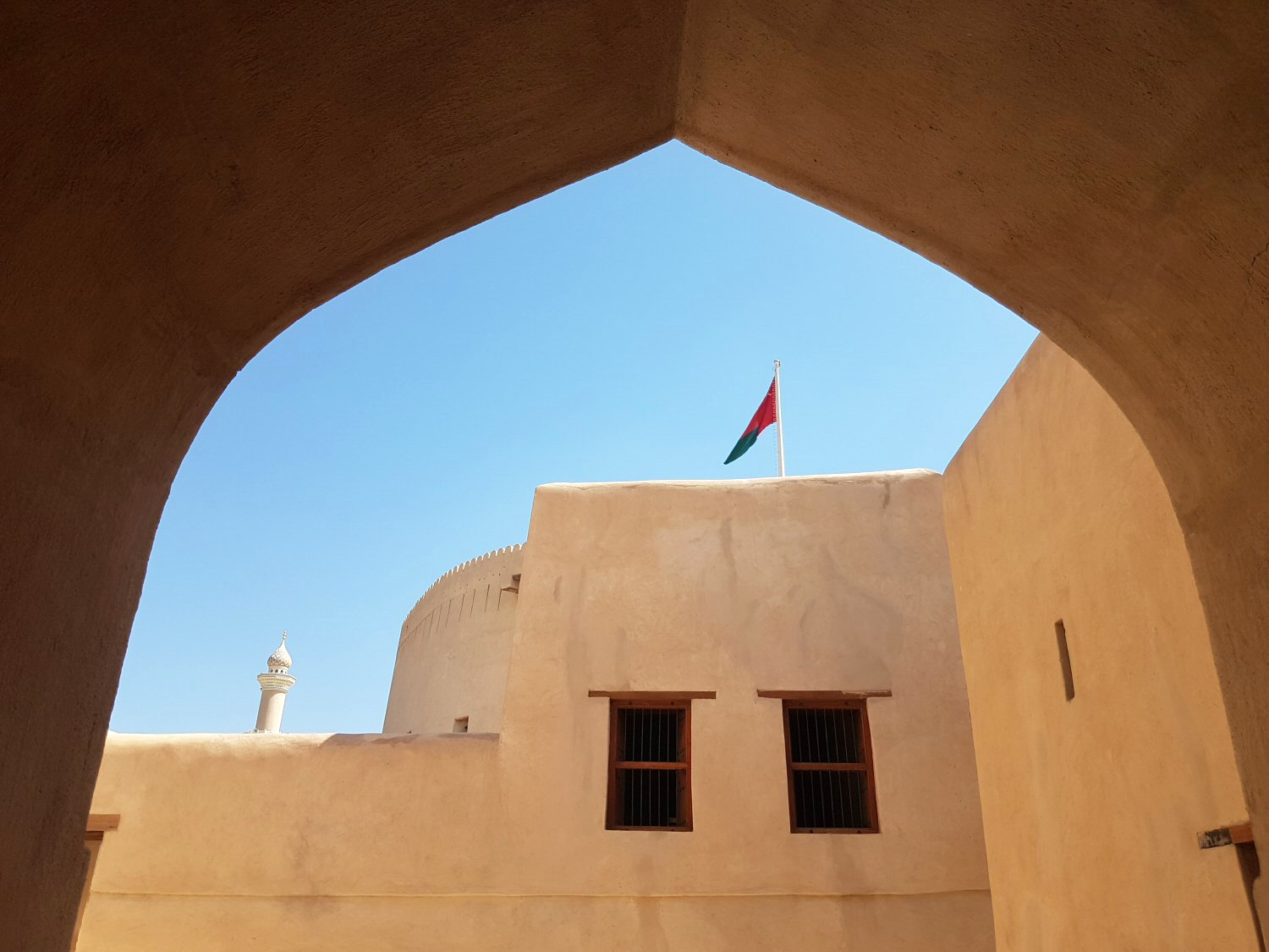 A view of a flag flying above the buildings of Nizwa fort in Oman seen through a pointed archway - my nine reasons to visit Oman with kids