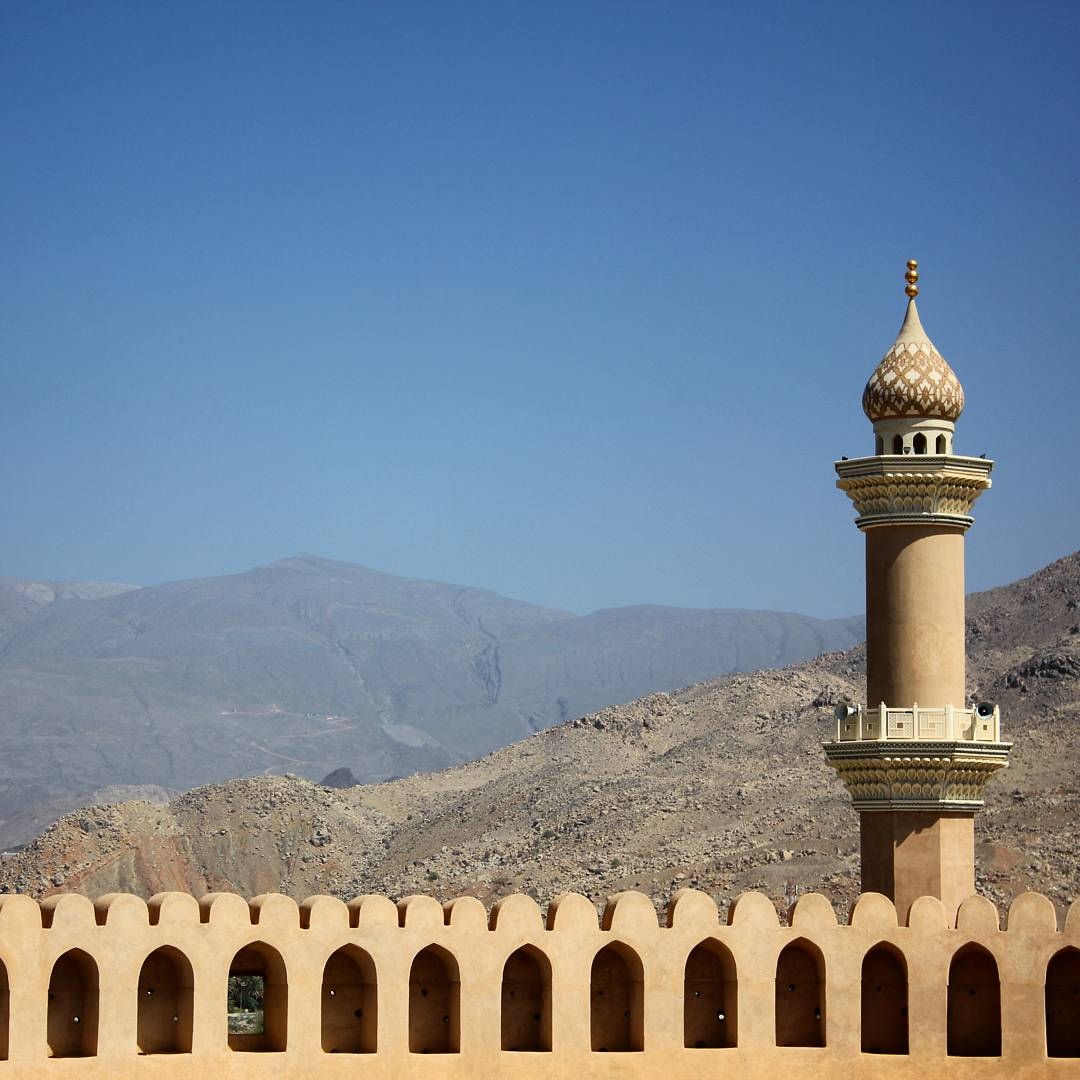 A view from Nizwa fort out onto the former capital of the interior in Oman, looking out across the golden arched fortifications to the minaret tower and Hajar mountains beyond - my nine reasons to visit Oman with kids