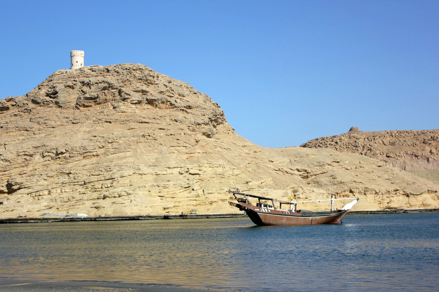 A wooden dhow boat in the water with a rock cliff behind at Sur in Oman - my nine reasons to visit Oman with kids