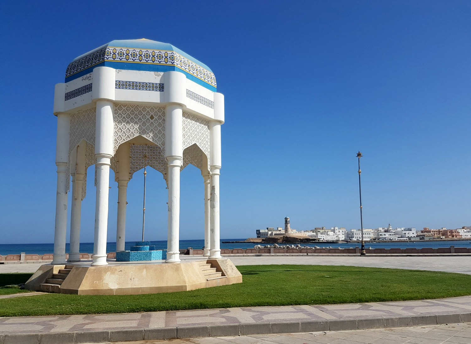A white and blue pavilion on the Corniche at Sur with the buildings across the water in the distance behind - my nine reasons to visit Oman with kids