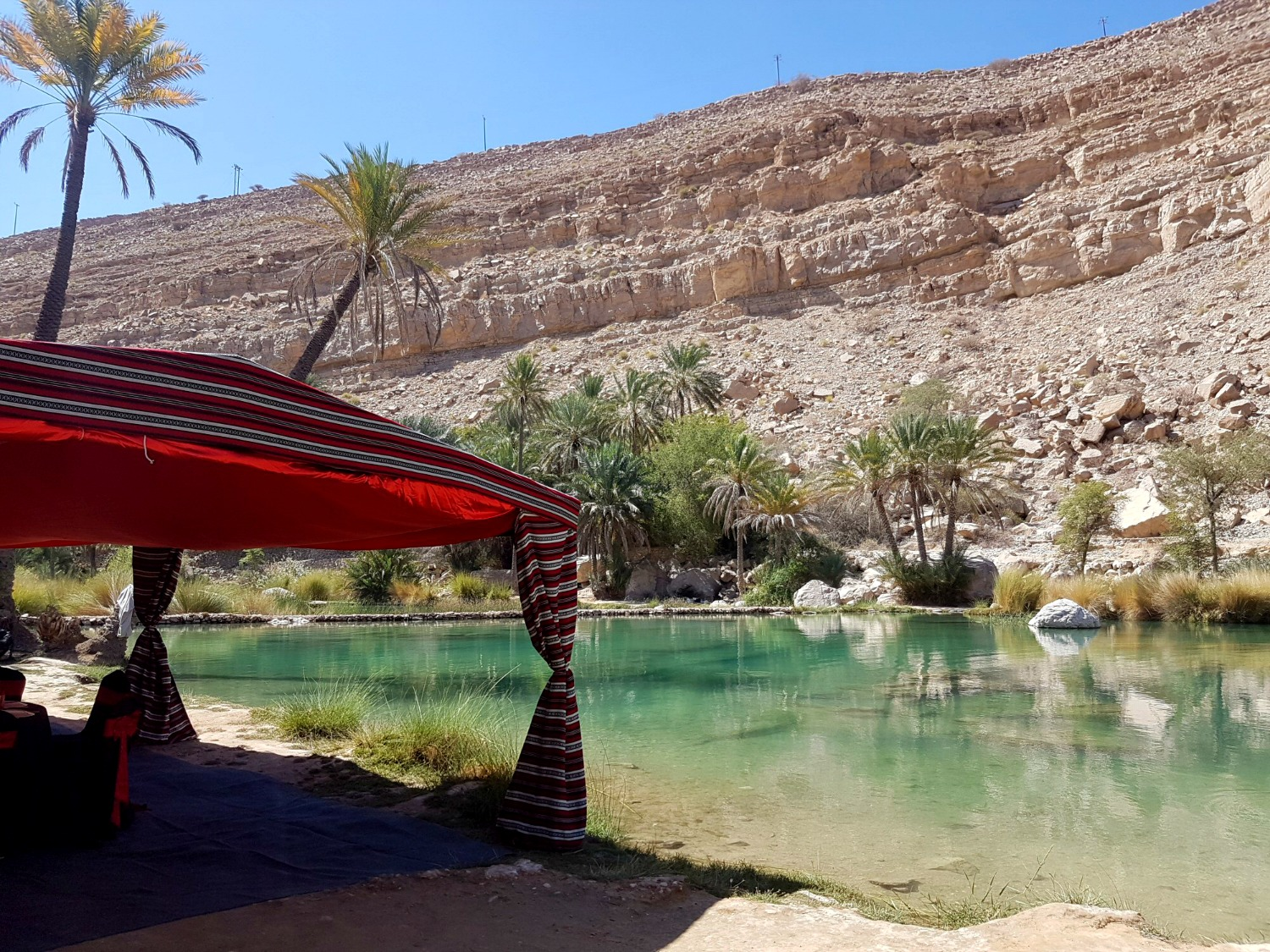 A red tent set up by the waters of Wadi Bani Khalid in the Hajar Mountains in Oman - my nine reasons to visit Oman with kids