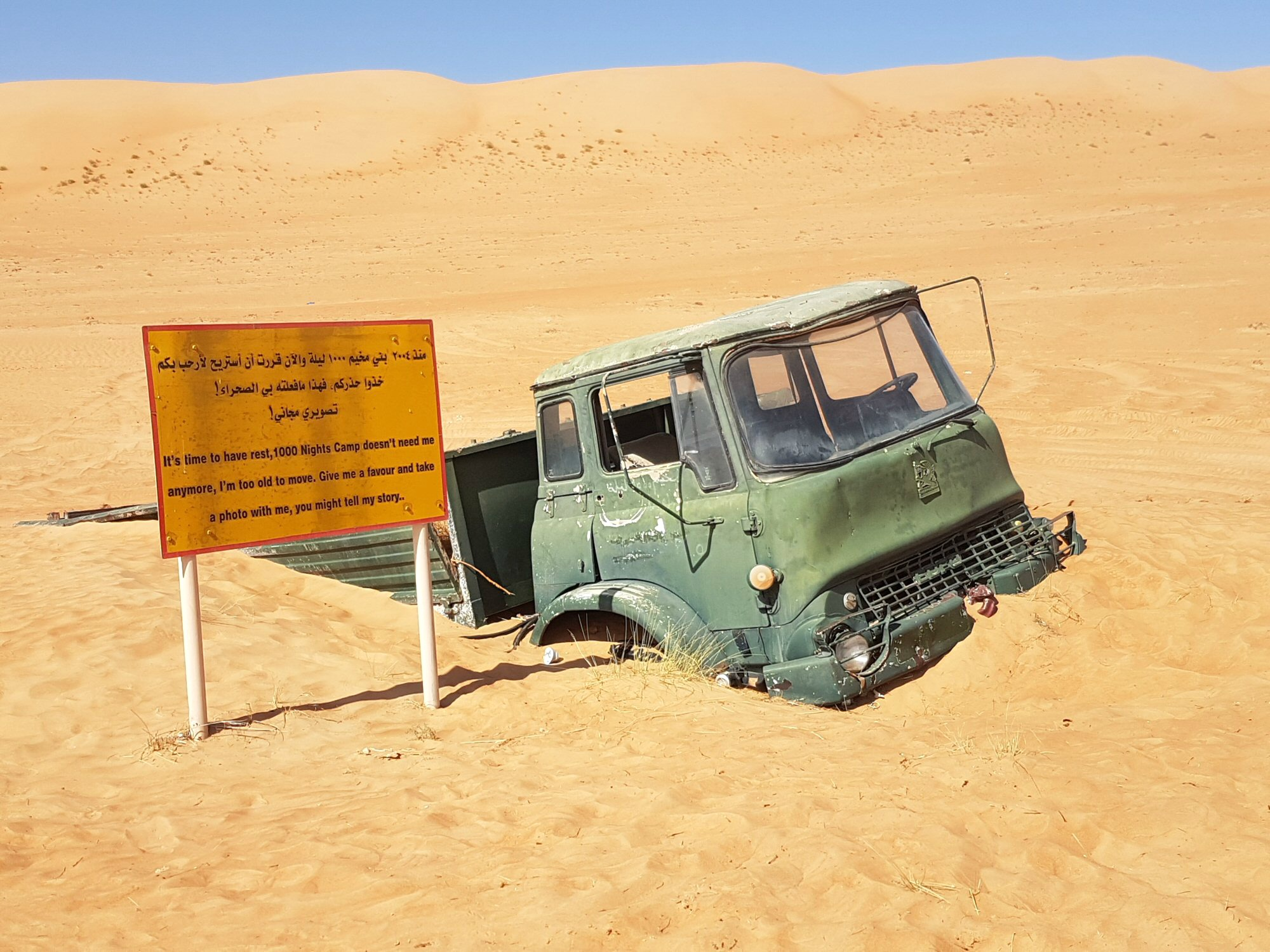 A half buried truck in the sand outside the 1000 Nights Camp at Wahiba Sands in Oman - my nine reasons to visit Oman with kids