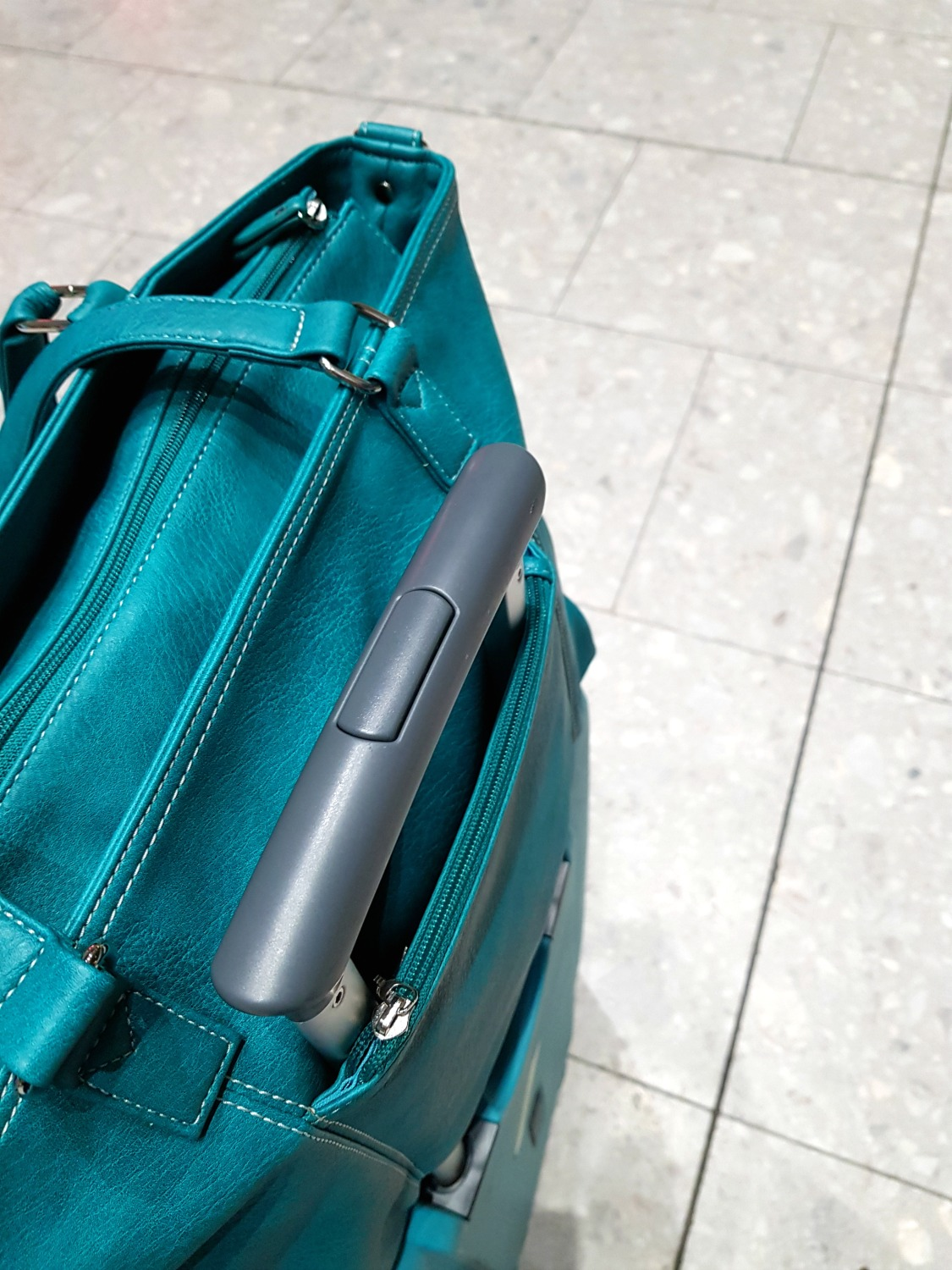 Green Mini Jen bag with special pocket slotting over the handles of a suitcase - my Mia Tui hand luggage review