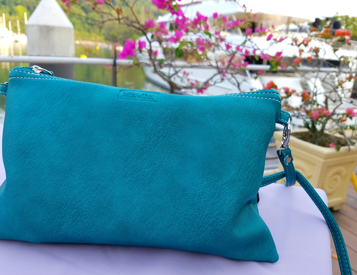 Mini Jen matching clutch bag on a table in a marina restaurant on Langkawi, pink flowers in the background - my Mia Tui hand luggage review