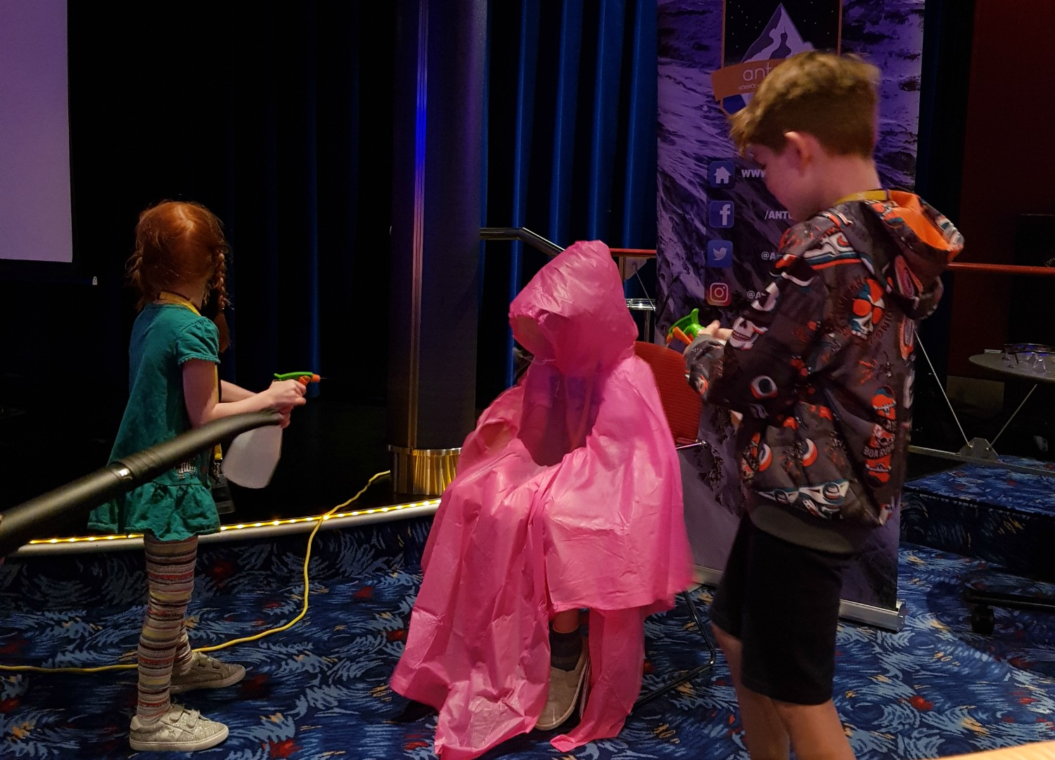 One brave volunteer in a pink poncho gets squirted with water to simulate a storm - testing out Anturus Explorer Academy kids club activities from Celebrity Cruises