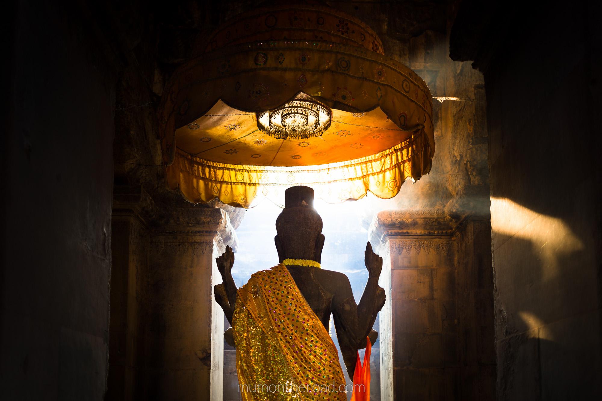 Bouddha au pied duquel des bouddhistes viennent se recueillir dans les couloirs d'Angkor Vat au Cambodge