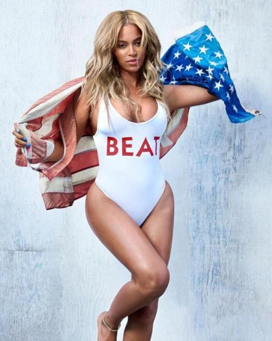 Beyoncé luce piel bronceada con un bañador blanco y decorado con la palabra 'Beat'.