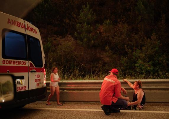 Un bombero, atendiendo a una mujer y una niña en estado de shock. FOTO:EFE