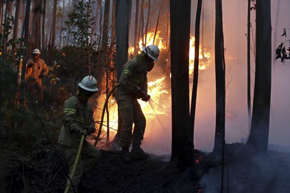Los bomberos, en plenas tareas de extinción del devastador incendio desatado en el centro de Portugal. FOTO: AP
