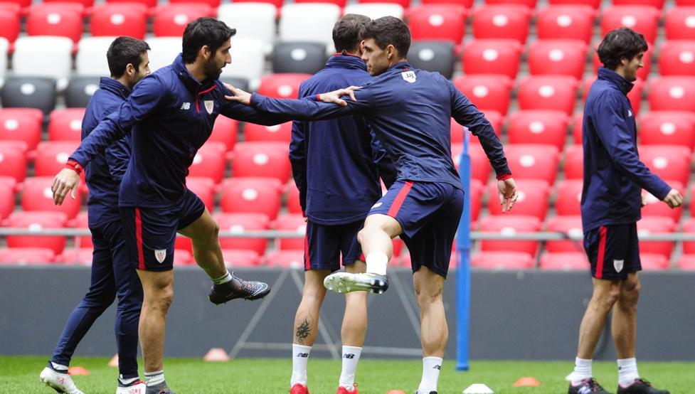 Óscar Gil se apoya en Raúl García para la realización de un ejercicio en el entrenamiento de este jueves.