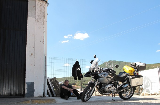 Biker sits on the floor against a fence in a petrol station, looks very hot