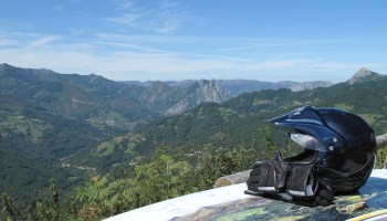 A motorcycle helmet and gloves rest on a panoramic guide at a lookout point in the Spanish mountains