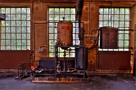 Various cylinders and pipes occupy the space in front of a windowed wall