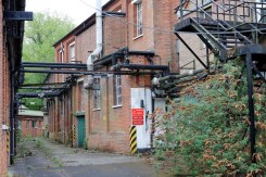 A narrow road leads off into the distance between two obviously derelict buildings