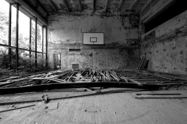Wide black and white interior shot showing a wrecked basketball court, the parquet floor at the far end pulled up and buckled