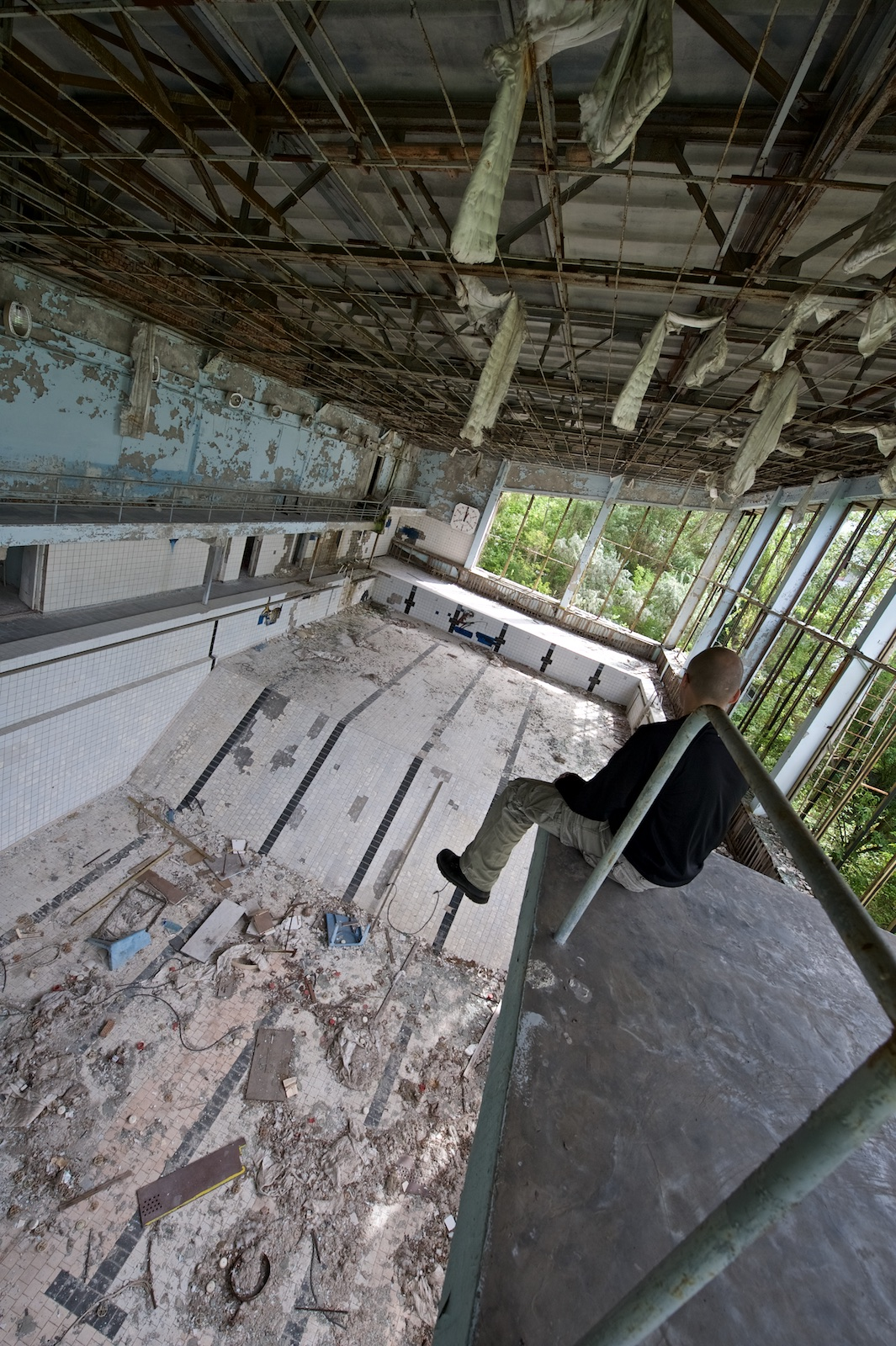 A bald guy sits on the top board at Pripyat's pool