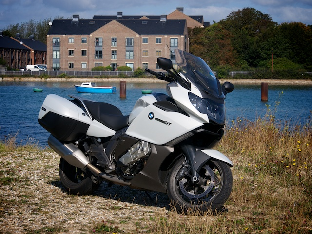 BMW K1600GT in front of some water with a little blue boat in it