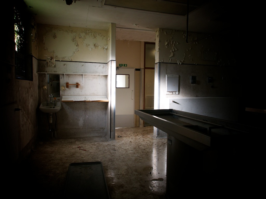 Light enters through a small window and lights up what could be a mortuary slab in an otherwise dark room