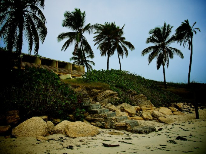 View looking up a beach, a derelict structure sits beneath palms on a moody horizon