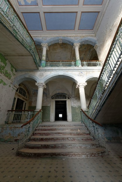 Two floors peek through arched columns onto a grand staircase covered in peeling paint