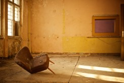 A chair with one broken leg lists mournfully in a room that is altogether far too yellow