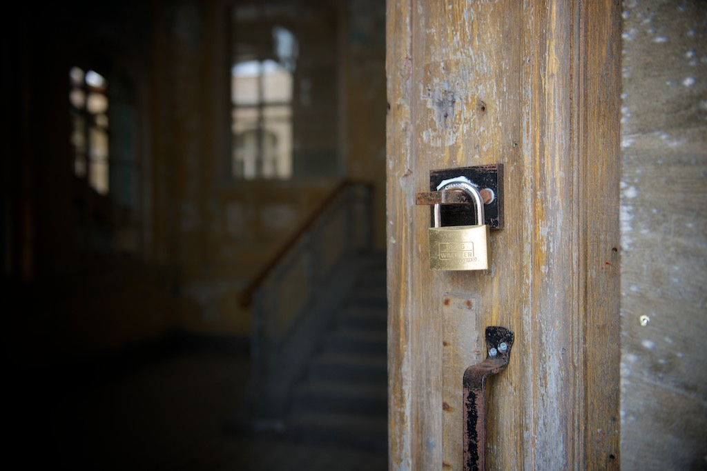 A small brass padlock hangs on a catch on a wooden door which occupies half the frame, stairway just visible in dark hallway beyond