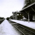 Black and white photo of and old train station, taken trackside looking at single storey ticket office