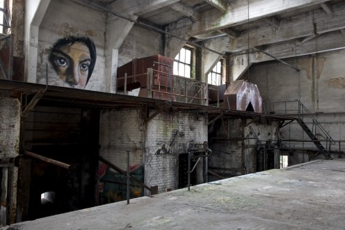 A girl's face has been painted to the side of the boilerhouse wall