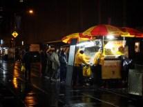 People queue at a hotdog stand at night