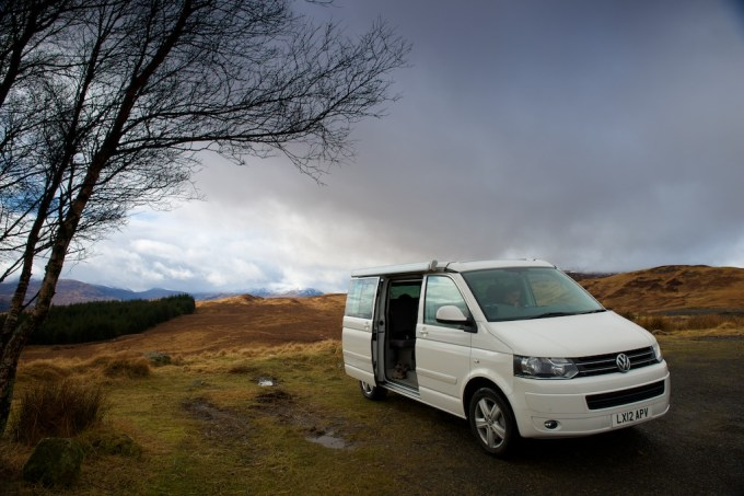 Side-on view of a white VW California camper van with side door open, parked in a Scottish valley