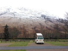 Lone camper van on a site in front of a snow-covered mountain