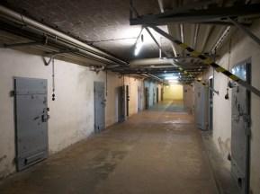 Cell doors line a dimly lit corridor