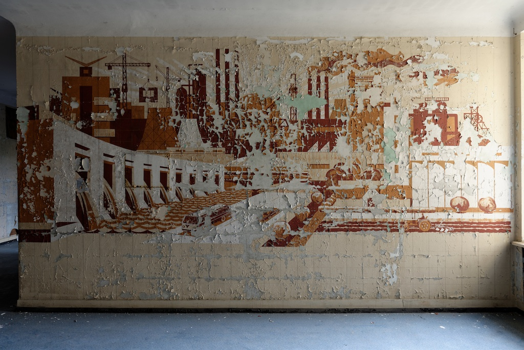 Propaganda communist still life mural of industrialised Russia slowly peels from a beige wall in a forgotten military relic