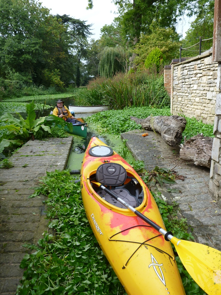 A yellow kayak prepares to be rolled down to the Thames from Abbey River, Chertsey