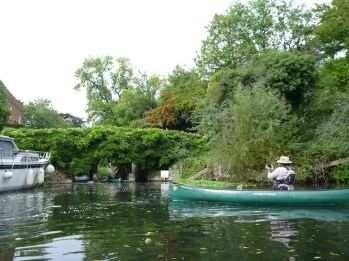 Canoe passes beneath wisteria on a small weir