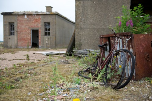 A pair of rusting bicycles lean against a shed in front of a smashed-up single storey building