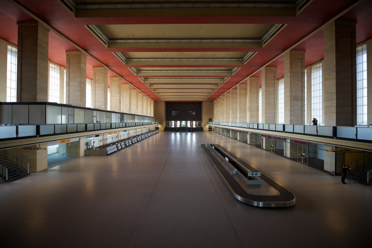 An empty arrivals / baggage reclaim hall in a vaguely art deco derelict airport