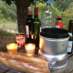 Two candles, some bottles of wine, and a cooker wait on picnic table