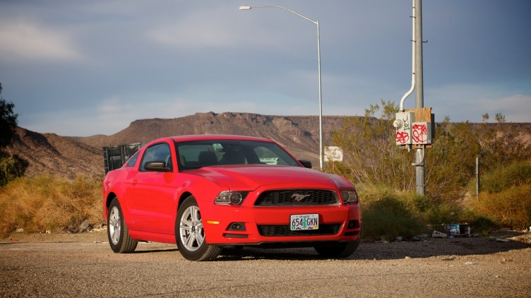 A red Ford Mustang parked in front of a gratified streetlight