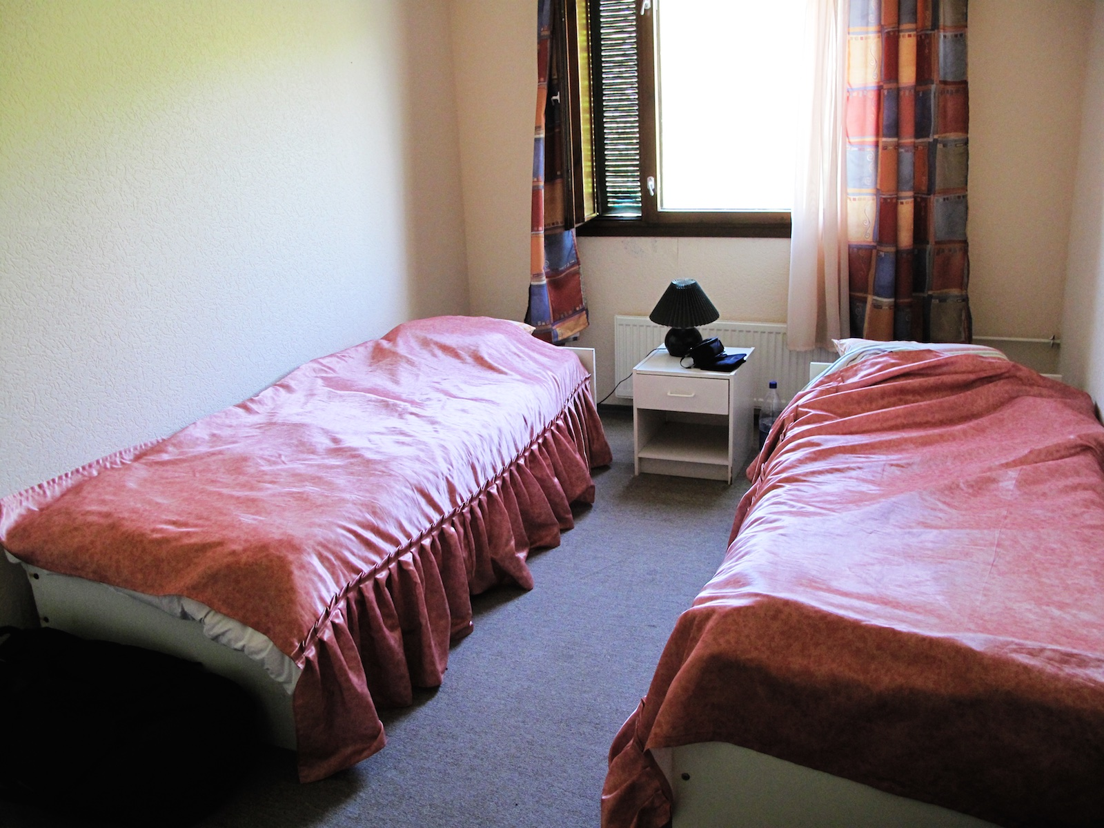 Weak photo showing two single beds and not much else in a narrow room