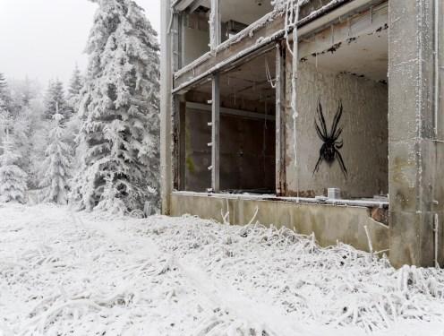 Broken windows look out onto a snowy landscape