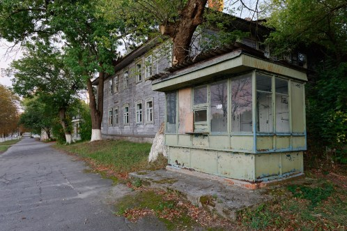 A small wood and glass kiosk in the foreground of a suburban street, peeling paint and no traffic