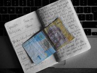 A colourful Ukrainian banknote holds place in a black and white notebook resting on the keyboard of a small Apple laptop